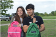 Two Teens Holding Backpacks