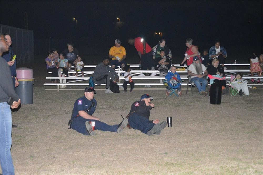Firefighters and Families Watching a Movie in the Park