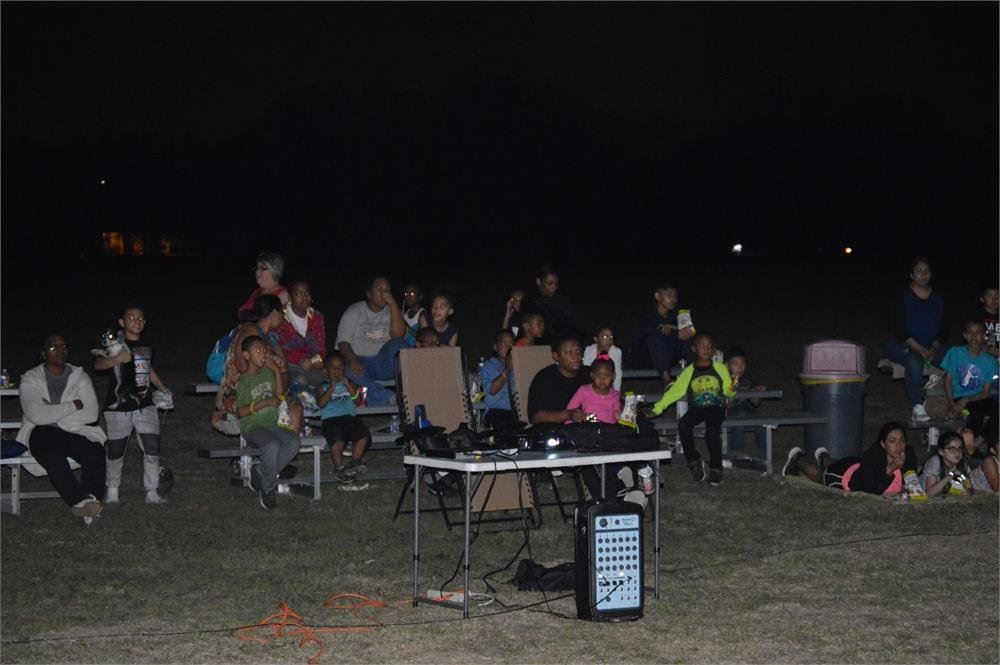 Kids and Adults Watching a Movie in the Park